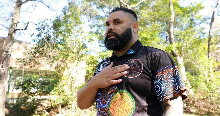 A man stands in the shade on a sunny day, with trees behind and around him.  He has his hand on his heart and is wearing a shirt with an Aboriginal artwork print on it.