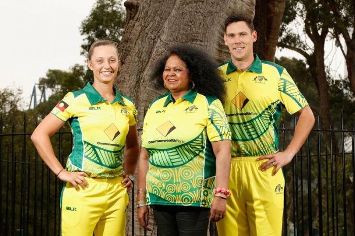 Three Indigenous people dressed in yellow and green cricketing uniforms featuring Indigenous design patterns. In the background is a tree and black iron fence.