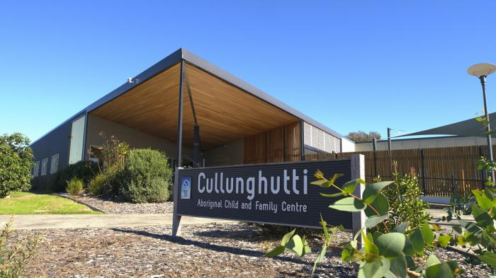 Large sign in foreground with the words Cullunghutti Aboriginal Children and Family Centre. In the background is a building with shrubs and around it. Behind the building is a sail and a clear blue sky.