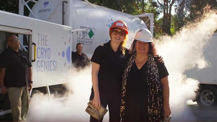 2 women are standing outside on a sunny day. They are wearing hardhats and smiling at the camera. In the background are 2 men, standing next to a large vehicle. White smoke is rising from the ground.