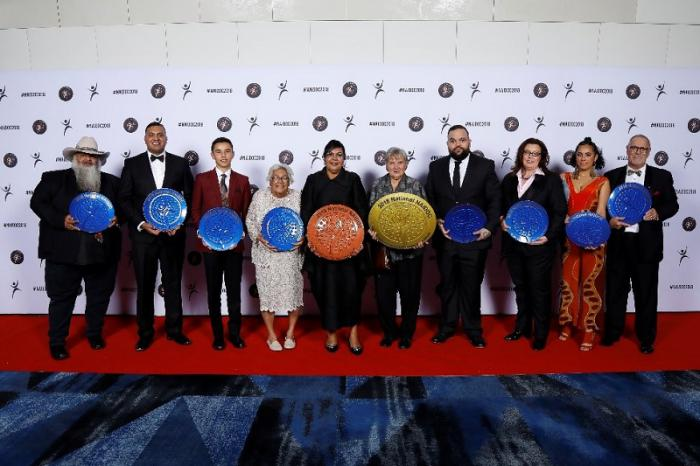12 award winners stand in a row with a logo photo wall behind, on the NAIDOC 2018 red carpet