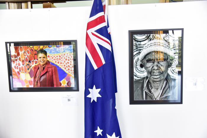2 portraits of women sit aside the Australian flag.