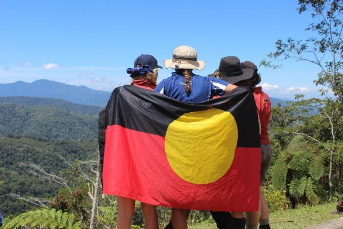 Four people wear hats look out over a valley with mountains in the background. They are wrapped in the Aboriginal flag that features a black panel above a red panel with a large yellow dot in the middle.