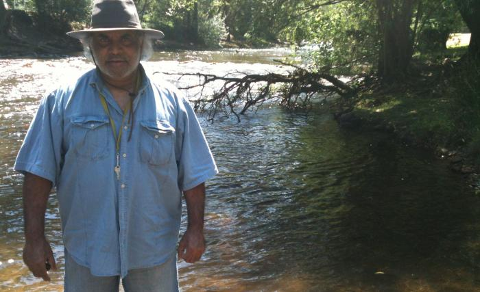 Dhudhuroa Elder Gary Murray standing in the Ovens River in Dhudhuroa Country