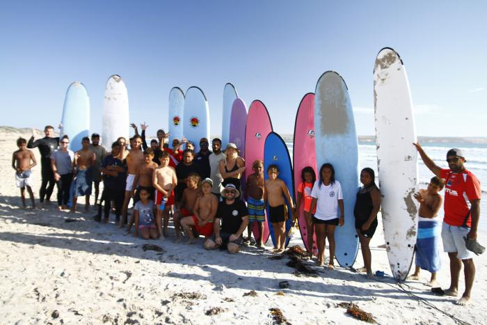 A large group of youth and adults stand on a beach with large surf boards on end, immediately behind them. In the background is the ocean and a cliff face.