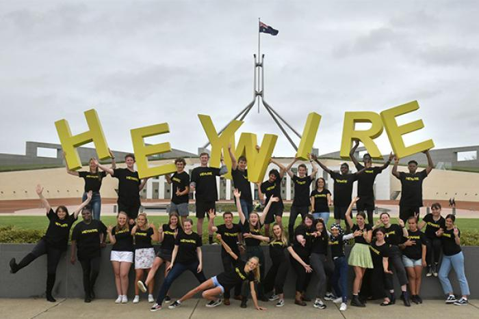 Two rows of youth in casual dress and wearing black t-shirts stand atop and in front of a wall. Some of those on the wall hold large yellow letters which spell: heywire.