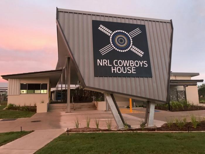 Building with a sign that reads NRL Cowboys House. In foreground is green grasss and concrete path.