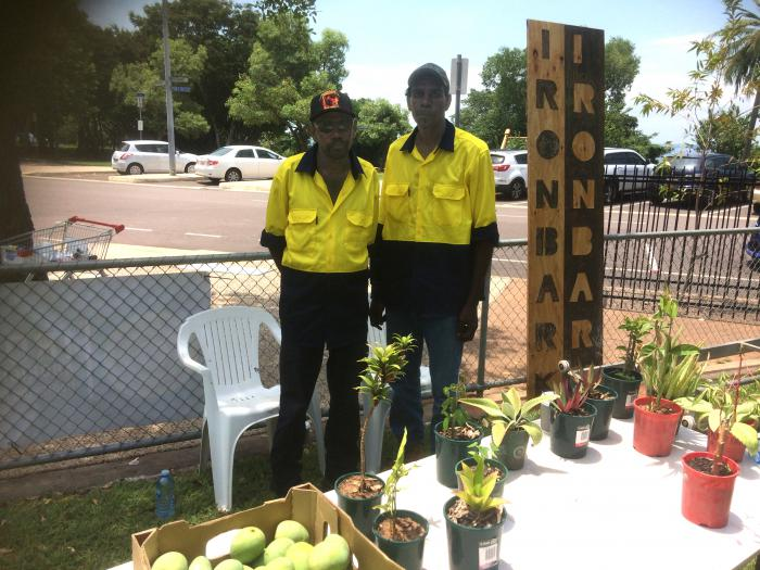 Two Aboriginal men standing outside in front of a table with pot plants and fruit. In the background there are trees and cars.