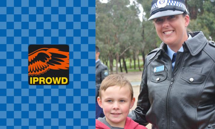 On the left, orange wings on black background with letters IPROWD beneath them all on light and dark blue checked background. On the right, a young boy in red and grey coat stands next to woman in police uniform.