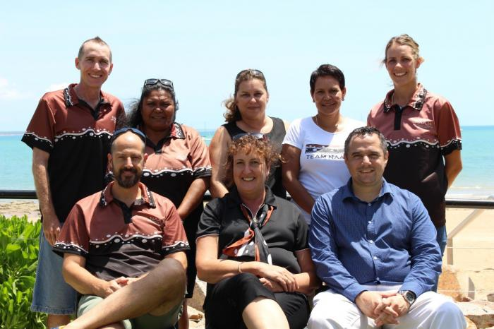 A group photograph of eight members of the North Australian Aboriginal Justice Agency (NAAJA).