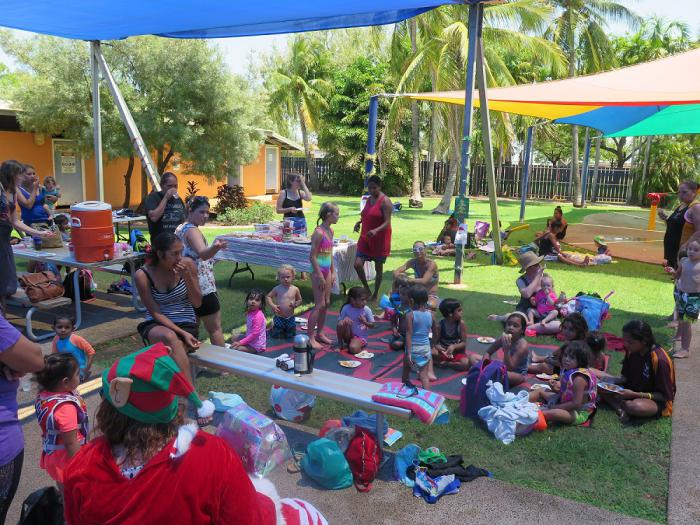 Large group of children and adults sit on grass and at tables under shade, dressed in swimming attire and other causal clothes. In the background are trees, shade covers and a building.
