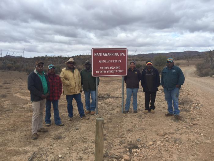 Seven Aboriginal men and women dressed in warm clothing stand next to a red sign just off a dirt road. In the background are bushes, trees and hills. The sign says Nantawarrina IPA – Australia's first IPA – Visitors welcome – No entry without permit.
