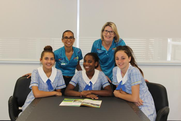 Two women in aqua coloured shirts stand behind three young women in pale blue school uniforms seated at a table.