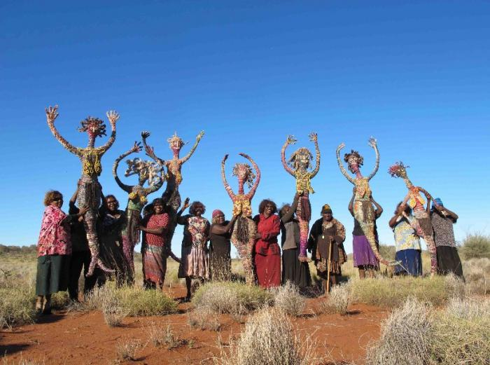 Thirteen Indigenous women stand in a line. They are holding up 7 life sized artistic figures of women.
