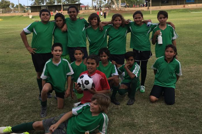 On a grass field is a group of 14 Aboriginal youth in green soccer jerseys and black shorts. The back row is standing, the middle row is kneeling and one young man lays down in front of the rest. One young man is in a red shirt and holds a soccer ball. In