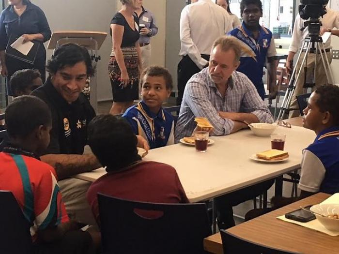 An Indigenous man and non-Indigenous man sit at a table with Indigenous children while other adults and an Indigenous boy stand in the background.