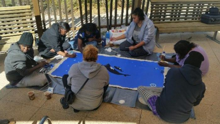 Seven Indigenous women sit on a tile floor inside a wooden shelter around a large painting of the blue ocean with black whales swimming.