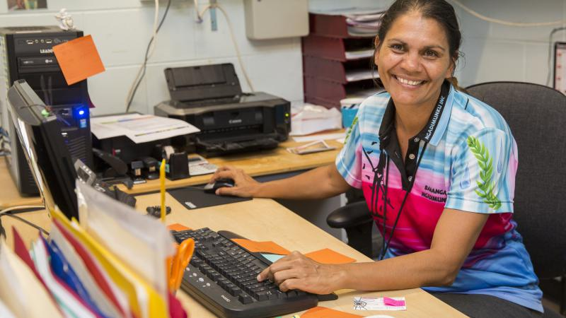 Indigenous woman sits at a desk with computer and printer atop. There are folders and pens in the foregroundj, a blue wall with pictures and powerpoints in the background.