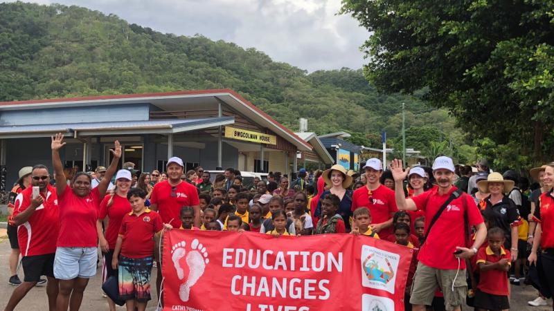A group of men, women and children in red school polo shirt with a crowd of Indigenous children behind red banner with white writing on banner 'Education Changes Lives.'