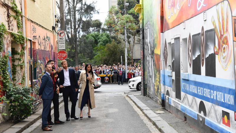 4 people (Duke and Duchess of Sussex, an aboriginal man Robert Young and third man) stand in an alley viewing colourful murals on the walls lining the alley. In the background are cars, a crowd of people, and trees behind the crowd.