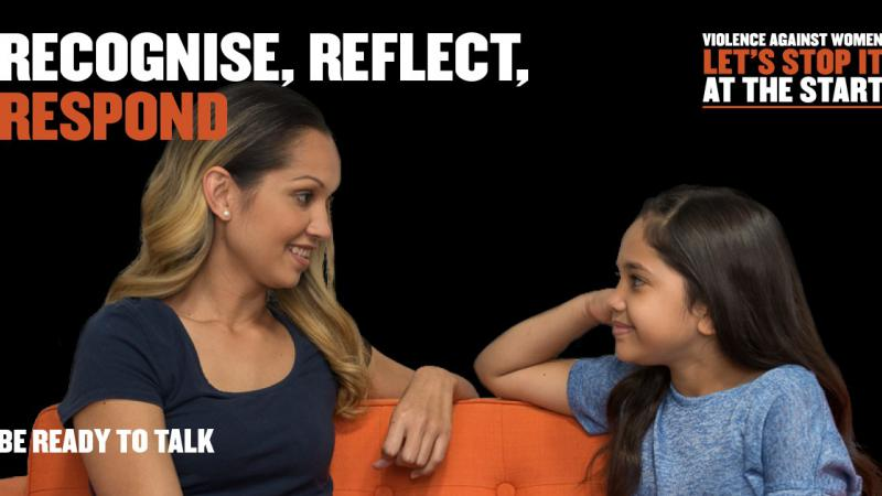 A woman sits on an orange couch facing a girl on the same couch. The background is black and included the words: Recognise, Reflect, Respond. Be ready to talk, Violence Against women. Let's stop it at the start.