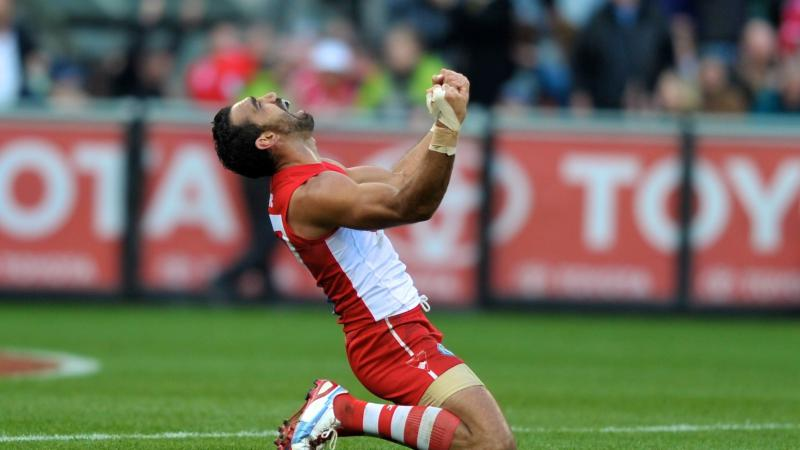 Footballer Adam Goodes is kneeling in the middle of an oval, triumphantly raising his hands in the air.