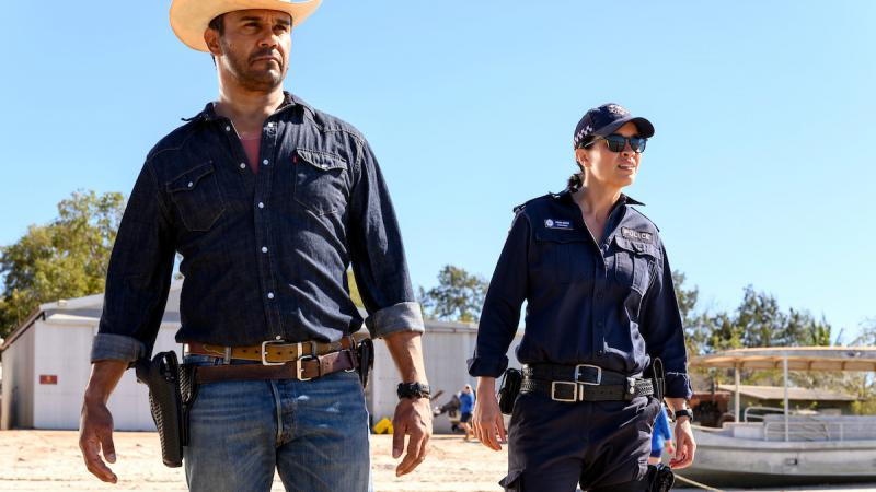 Two actors, a male and female are looking in the distance. The male is wearing a straw hat and weraing denim clothes, the female is dressed as a police officer.
