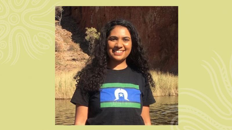 Indigenous woman with long black hair wearing a black t-shirt with a blue, green and white flag on the front stands in front of body of water. In the background is grass and a cliff face.