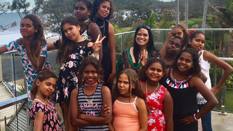 Aboriginal woman with a group of 12 year 5 and 6 Aboriginal girls. They are wearing colourful dresses, and a standing on a balcony with a beach behind them.