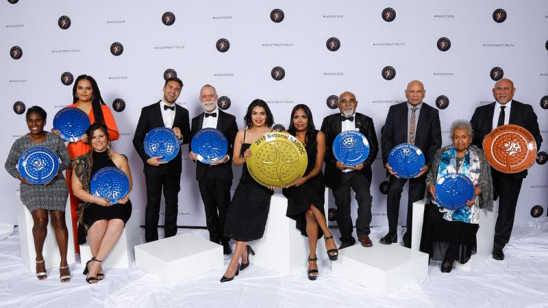 A group of 11 men and women in a row, they each hold an award.