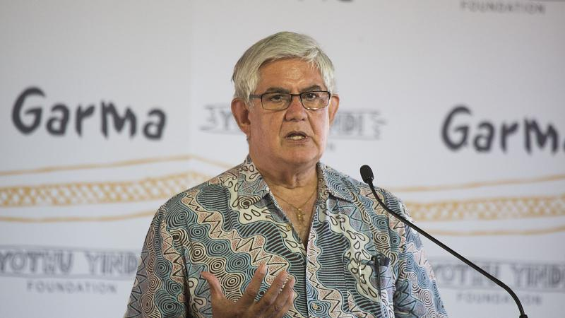 Elderly man with grey hair wearing glasses and an open neck shirt with Indigenous designs stands at a pulpit with micropone. The backdrop is white with the words: Garma, Yothu Yindi Foundation and some long wavy orange lines.