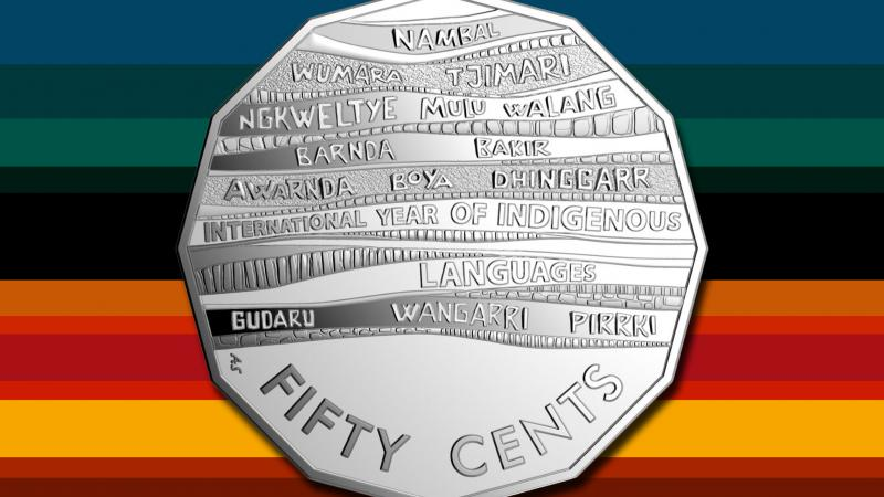 Silver sharp sided coin featuring the words Fifty Cents and multiple Indigenous Australian names on a background of horizontal stripes on many different colours.