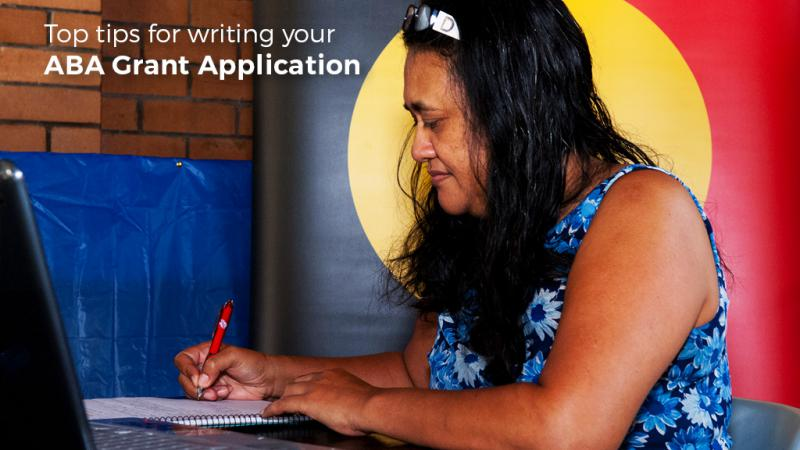 Indigenous woman writing on paper with a pen and the Aboriginal flag in the background, a laptop computer in the foreground and the following words displayed: Top tips for writing your Aboriginal Benefit Grant Application