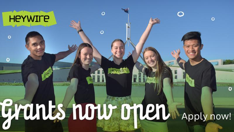 Text overlay: Heywire Grants now open. Apply Now. 5 young people stand in front of Parliament House.