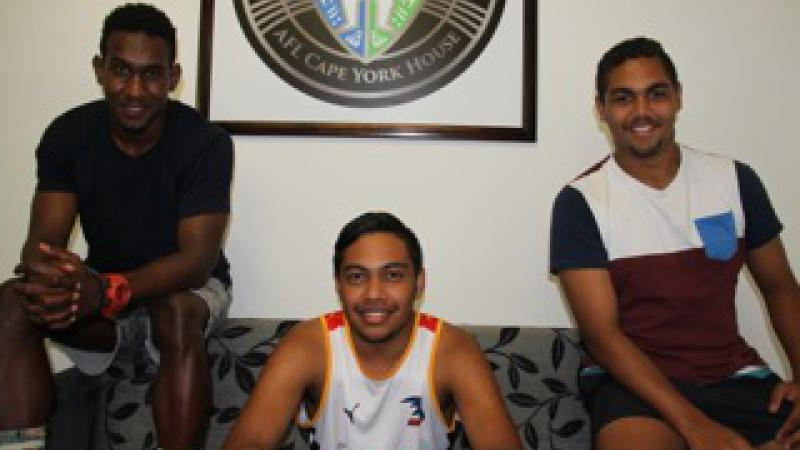 Three young Indigenous men sitting on a couch and smiling.