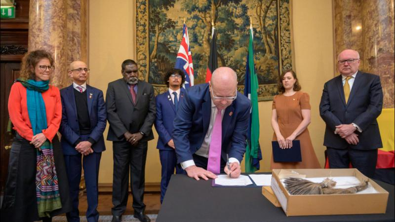 Balding man in suit and glasses signs a document on a table next to some Indigenous artefacts. In the background are 6 people dressed in formal wear and behind them are flags and wall hangings.