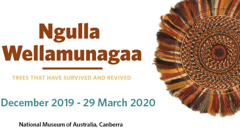 White tile with multi-brown coloured circular mat at right. At left are the words: Ngulla Wellamunuagaa, Trees that have survived and revived. 5 December 2019 - 29 March 2020, National Museum of Australia, Canberra