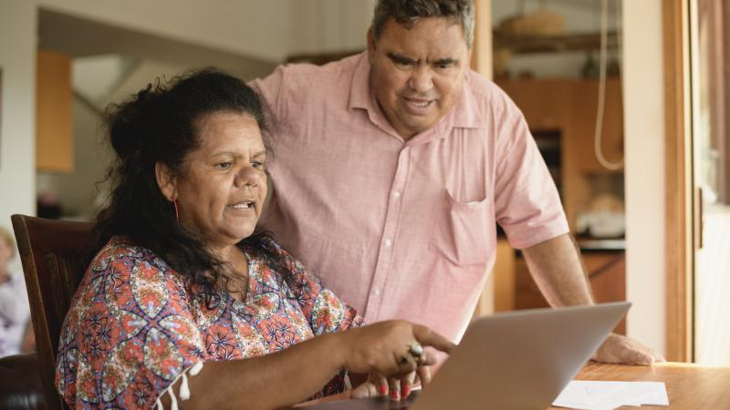 An Indigenous woman in a colourful dress sits at a table and points at the screen of a laptop with an Indigenous man in pale apricot coloured shirt looking at the same.