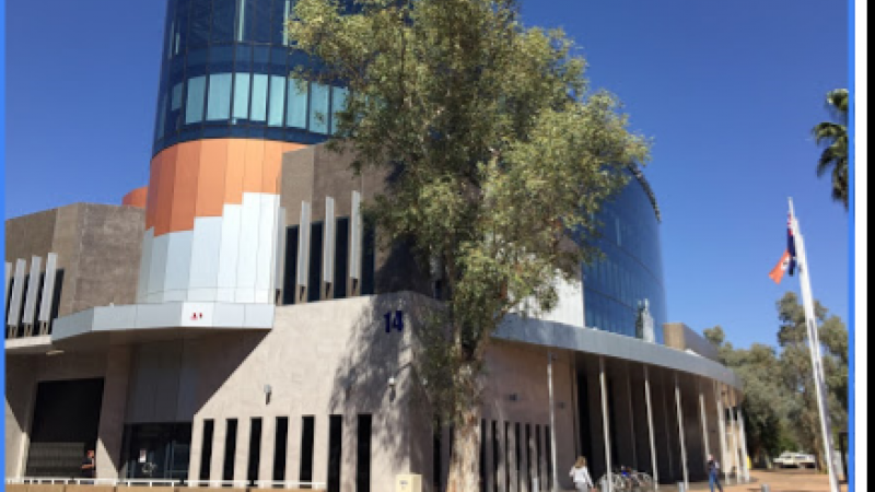 Blue, orange, white and beige building with tree in front and footpath with pavers in front of that. Aboriginal flag at right.
