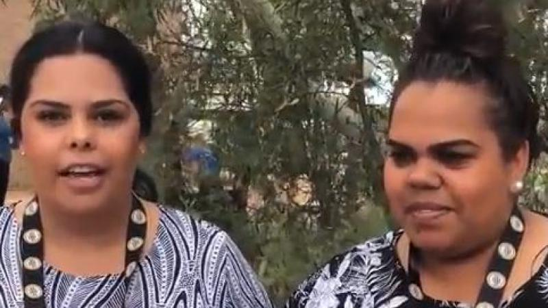 Two Indigenous women in black and white clothing stand in front of trees.