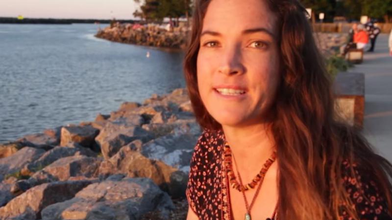 A head and shoulders photo of a woman with long brown hair and necklaces. In the background is water, rocks lining the water, trees and a footpath.