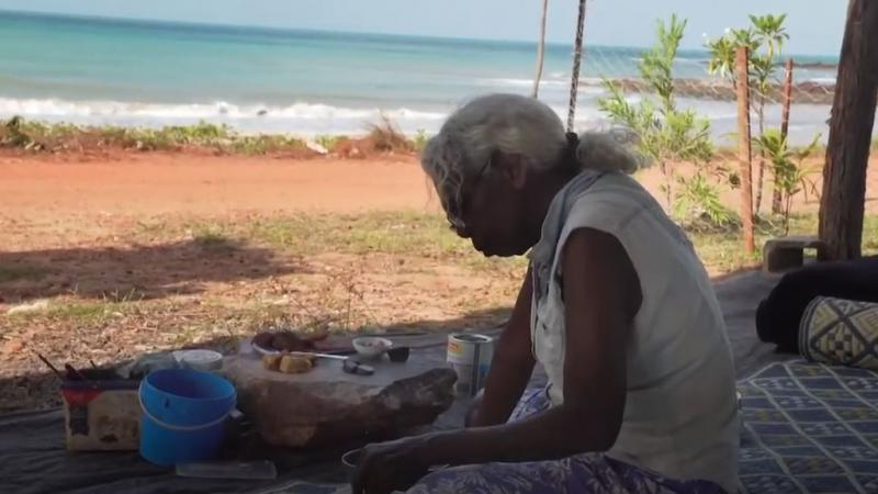 An elderly woman with grey hair sits on a mat with painting equipment in front of her. In the background is red soil, grass, a shrub and the ocean.