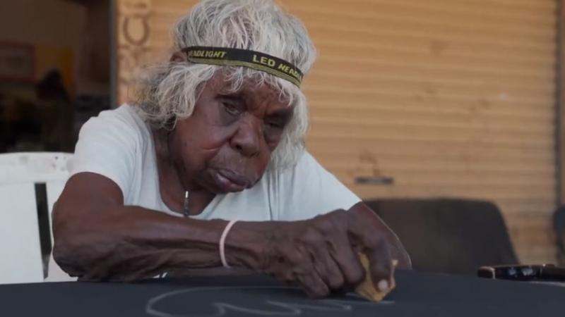 An elderly Aboriginal woman wearing a headband around her grey hair sits at a table and sketches on a black canvas.