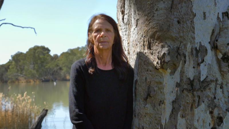 An elderly woman with dark long hair and wearing a dark top stands next to a gum tree. In the background are water and trees.