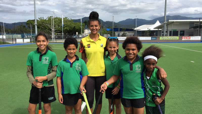 A young adult Indigenous woman in yellow shirt and black pants stands between five Indigenous children dressed in green shirts and black shorts. All stand on a flat green playing surface. In the background are poles, and buildings.