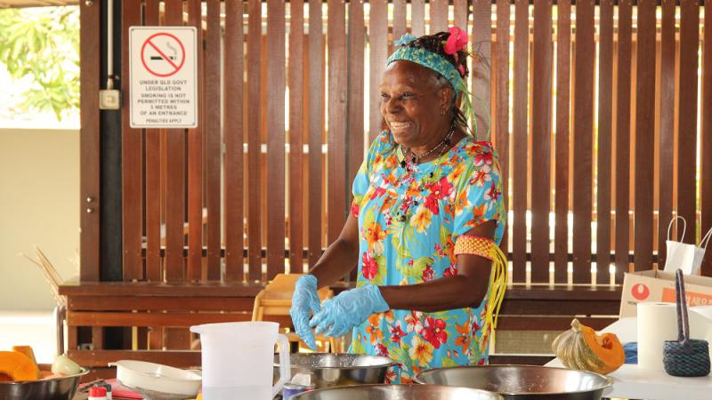 Indigenous woman in colourful dress stands behind a bench covered with cooking apparatus. Behind her is a wall of wooden slats.