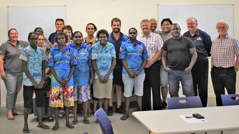 Large group of Indigenous and non-Indigenous men and women dressed in casual clothing in a room with beige carpet. In the background is a pale yellow wall and two whiteboards. In the foreground is a white table and blue chairs.