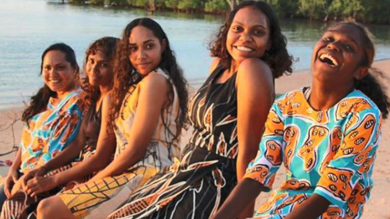 Five Indigenous women wearing colourful clothing sit in a line on a beach with water and trees in the background.
