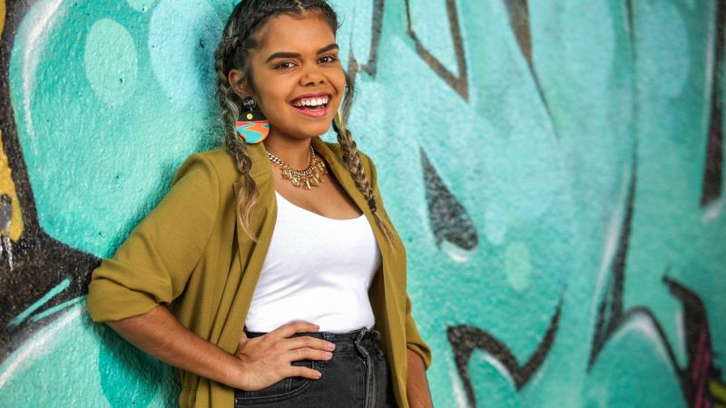An Indigenous young adult woman, her hair plaited and wearing a green yellow cardigan, white top  and black jeans, leans up against a wall painted black and with an aqua coloured mural.