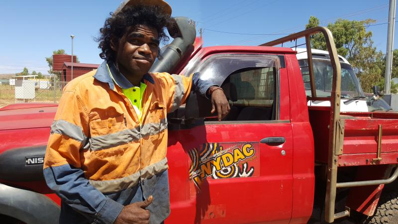 A young Indigenous man dressed in work wear stands in front of a red truck with the letters WYDAC on the cab door. In the background is a white vehicle, trees and buildings.